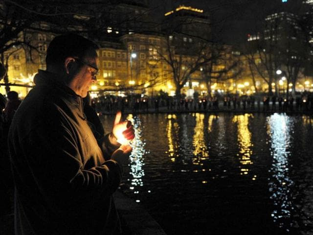 A-man-holds-a-candle-as-he-joins-others-around-the-pond-in-the-Public-Garden-after-a-candlelight-interfaith-service-at-Arlington-Street-Church-in-Boston-AFP