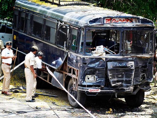 Policemen-secure-the-area-around-a-damaged-police-bus-after-an-explosion-in-a-residential-neighborhood-near-the-office-of-BJP-in-Bangalore-AP