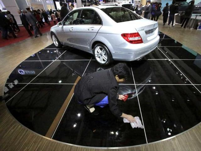A cleaner wipes the floor where Mercedes Benz C260 is displayed at the Shanghai International Automobile Industry Exhibition media day in Shanghai, China. AP