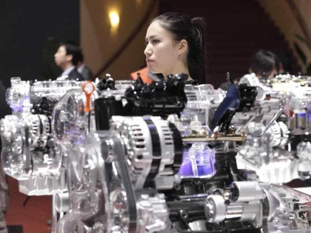 A model stands next to a skeleton model of an engine displayed at the Shanghai International Automobile Industry Exhibition media day in Shanghai, China. AP