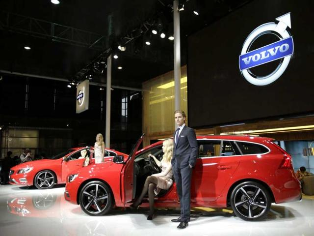 Models pose next to a Volvo S60 R-Design at the Shanghai International Automobile Industry Exhibition media day in Shanghai, China. AP