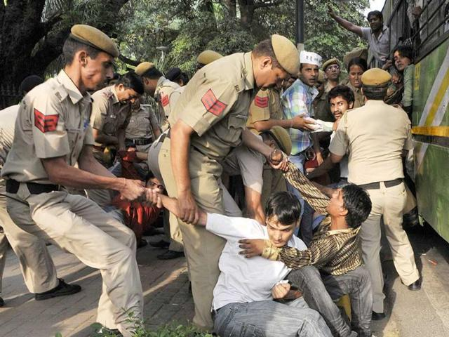Security personnel try to remove protestors of AAM Party shouting slogans outside Prime Minister