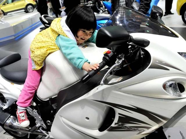 This photo taken on April 20, 2013 shows a young girl sitting on a Honda GSX1300R 'Hayabusa'on media day at the Shanghai auto show. The Shanghai auto show, which opens to the public on April 21, is expected to attract more than 800,000 visitors over the course of nine days. Photo:AFP