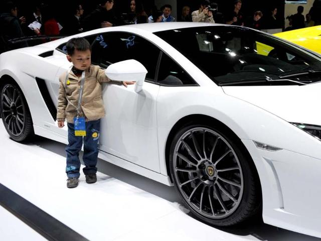 This photo taken on April 20, 2013 shows a young boy standing next to a Lamborghini Gallardo LP560-2 on display on media day at the Shanghai auto show. The Shanghai auto show, which opens to the public on April 21, is expected to attract more than 800,000 visitors over the course of nine days. Photo:AFP