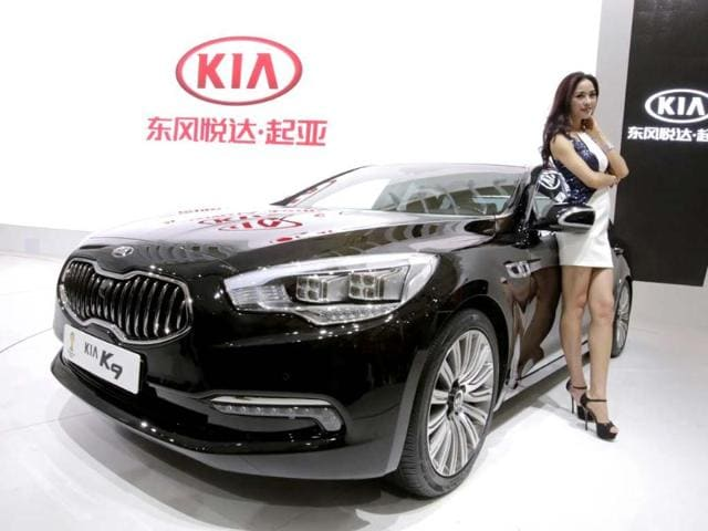 A model poses with a KIA K9 car at the Shanghai International Automobile Industry Exhibition (AUTO Shanghai) in Shanghai, China Sunday, April 21, 2013. Photo: AP