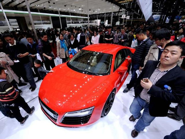 Visitors look at an Audi R8 V8 on the opening day of the Shanghai auto show on April 21, 2013. Chinese buyers swarmed around hundreds of vehicles at the Shanghai auto show at its opening highlighting the importance of the world's largest car market to manufacturers. Photo: AFP