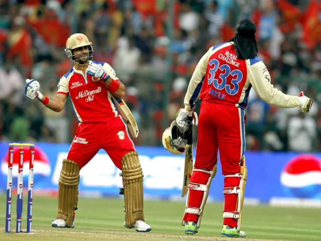 Royal Challengers Bangalore Chris Gayle, with Virat Kohli, reacts after completing 150 runs against Pune Warriors during the T20 match at Chinnaswamy Stadium in Bangalore. (Sanjeev Verma/HT)