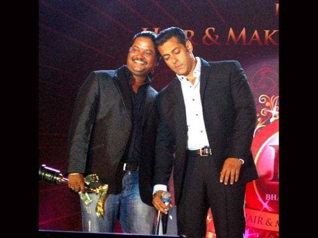 Bollywood actor Salman Khan presenting award to make-up man Raju Nag during the Hair Styling and Make up Awards 2013, in Mumbai on Monday night. Bharat and Dorris Godambe, owner of cosmetics brand, B & D have completed 25 years in the profession. (UNI Photo)