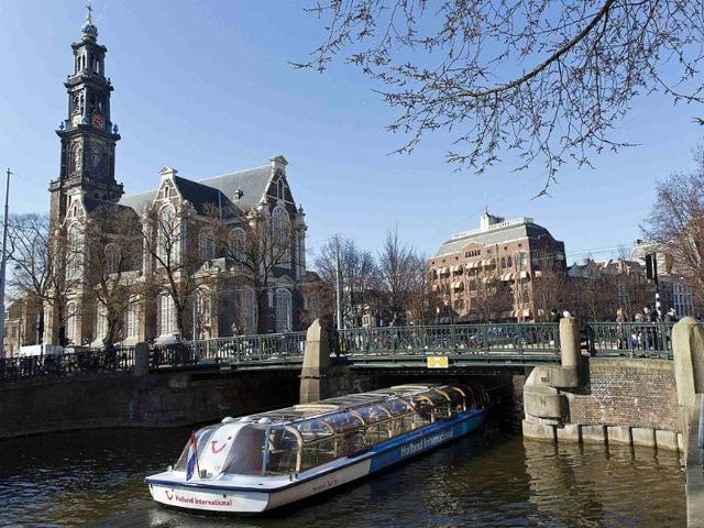 A-tourist-boat-passes-under-a-bridge-next-to-the-Westerkerk-church-in-Amsterdam-Photo-Reuters-Michael-Kooren