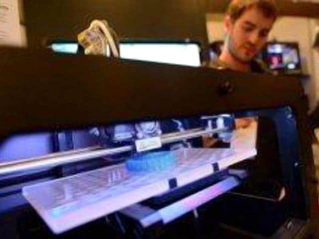 Visitors-look-at-a-3D-printer-printing-an-object-during-an-exhibition-in-New-York-AFP-Emmanuel-Dunand