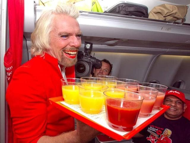 British-billionaire-Richard-Branson-serves-drinks-as-a-flight-attendant-onboard-an-AirAsia-flight-bound-for-Kualu-Lumpur-at-Perth-Airport-AFP