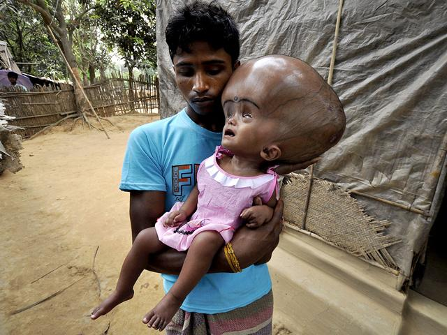 Abdul-Rahman-holds-his-18-month-old-daughter-Roona-Begum-in-the-village-of-Jirania-on-the-outskirts-of-Agartala-AFP-PHOTO-Arindam-Dey