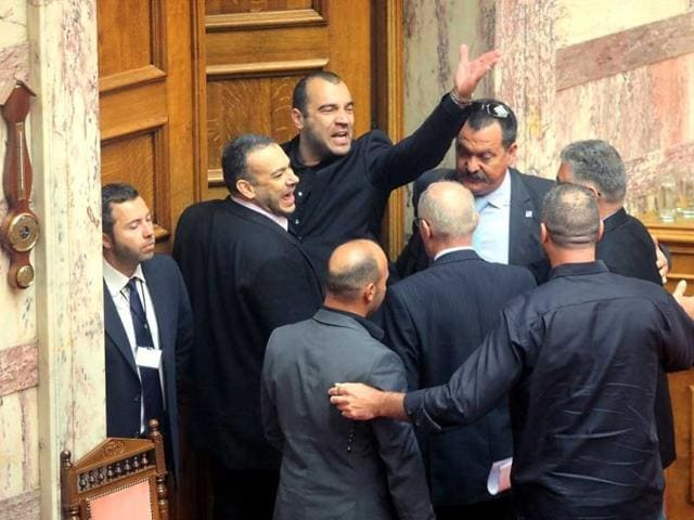 Golden-Dawn-MP-Panagiotis-Iliopoulos-C-gesturing-shouts-in-the-Greek-parliament-as-he-was-ordered-out-by-the-acting-speaker-after-he-poked-fun-at-the-leader-of-the-main-leftist-opposition-Syriza-party-AFP-photo