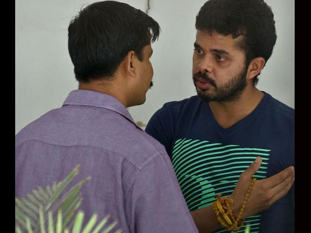 Shanthakumaran-Sreesanth-R-gestures-to-a-Delhi-Police-Special-Cell-official-before-being-taken-to-court-in-New-Delhi-AFP-Photo