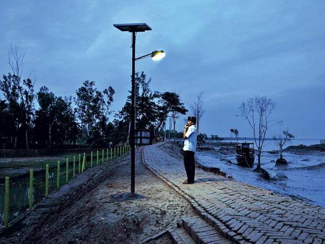 Solar-lamps-draw-the-line-between-human-babitat-and-tiger-territory-in-the-Sunderbans-A-man-stands-below-one-such-lamp-on-the-banks-of-river-Gomor-Subhendu-Gosh-HT-photo