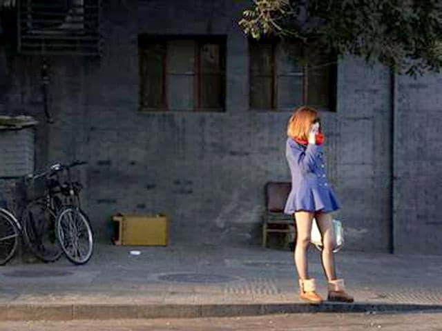A-woman-wearing-bright-colourful-clothes-talks-on-her-mobile-phone-in-central-Beijing-Reuters-Photo
