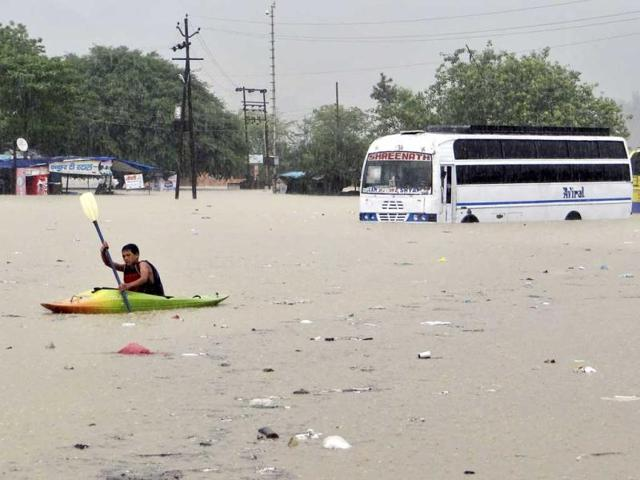 A-man-rows-past-a-bus-partly-submerged-in-flood-water-in-Rishikesh-Uttarakhand-AP-Photo