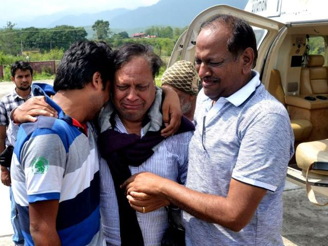 Pilgrims that were evacuated from a flood hit area by helicopter hug family members after arriving in Dehradun. (AFP)