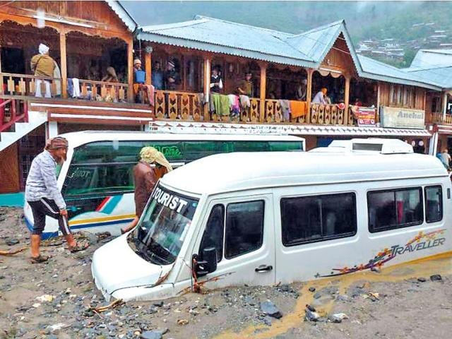 Residents and travellers walk past vehicles stranded by silt deposited by floodwaters in Uttarakhand