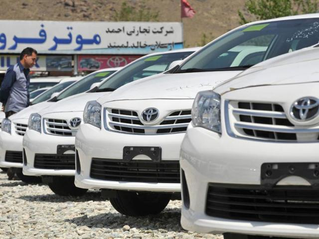 In-a-picture-taken-on-April-22-2013-a-potential-Afghan-customer-browses-through-parked-Toyota-Corolla-cars-at-an-auto-dealership-in-Kabul-Cheap-robust-and-reliable-consumer-culture-may-be-relatively-new-to-Afghanistan-but-when-it-comes-to-cars-there-is-a-clear-favourite-the-trusty-Toyota-Corolla-In-a-country-where-even-paved-roads-in-the-smartest-parts-of-the-capital-are-riddled-with-pot-holes-the-sturdy-Japanese-made-car-is-the-vehicle-of-choice-for-all-but-the-richest--Photo-AFP-Manjunath-Kira