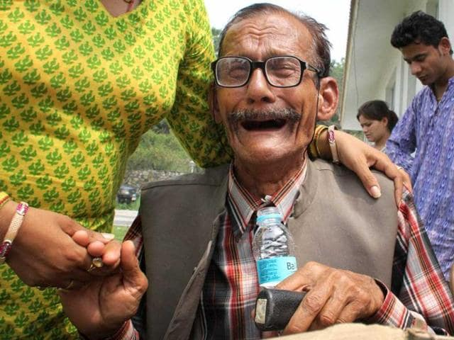 An-elderly-stranded-pilgrim-is-consoled-by-his-relative-after-being-rescued-from-the-upper-reaches-of-Uttarakhand-in-Dehradun-PTI