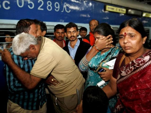 Pilgrim Rahava Chary, second from left, who was stranded after flash floods and landslides in Uttarakhand, hugs his family members on his arrival in Hyderabad. (AP Photo/Mahesh Kumar A)