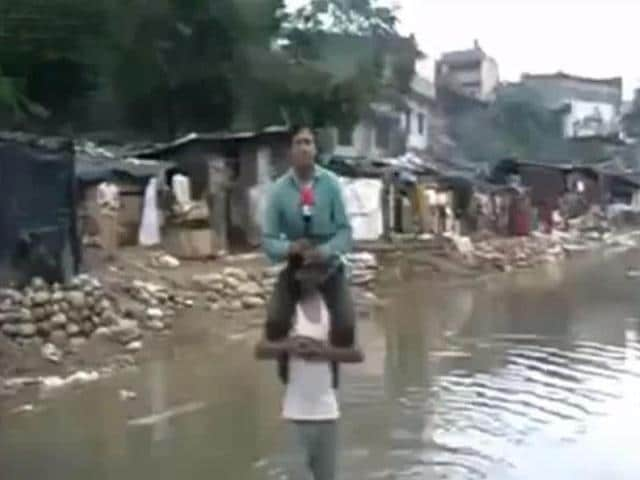 A-video-grab-from-the-YouTube-video-that-shows-a-local-Uttarakhand-journalist-reporting-the-deadly-floods-perched-on-the-shoulders-of-a-victim