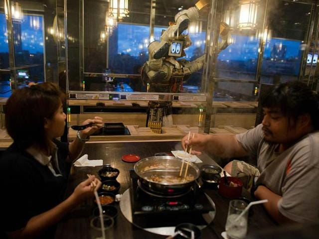 Costumers-being-served-by-a-robot-at-the-Hajime-robot-restaurant-in-Bangkok-From-chickens-catapulted-across-tables-and-service-by-robots-to-meals-dished-up-with-a-generous-portion-of-sexual-health-advice-Bangkok-is-doing-a-roaring-trade-in-unusual-dining-experiences-Photo-AFP-Nicolas-Asfouri