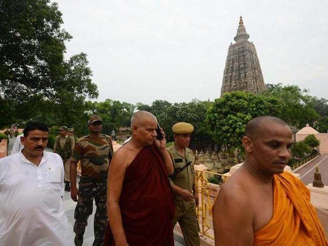 Buddhist monks and security officers walk after a blast on the campus of the Mahabodhi Temple in Bodhgaya, about 140kms southwest of Patna. AP