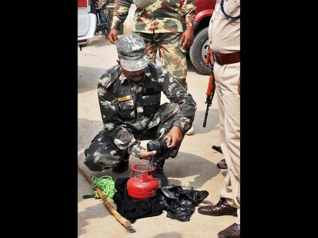 Security personnel handling a cane bomb, recovered from Buddhist Tergar Monastery at the Mahabodhi Temple in Bodh Gaya. PTI
