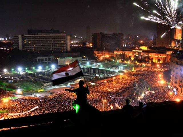 Egyptians-wave-the-national-flag-on-a-building-rooftop-as-thousands-flood-Egypt-s-landmark-Tahrir-square-to-demontrate-against-ousted-President-Mohammed-Morsi-and-in-support-of-the-Egyptian-Army-in-Cairo-AFP
