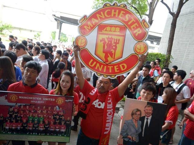 Manchester-United-fans-hold-posters-as-team-players-arrive-at-Don-Muang-International-airport-in-Bangkok-ahead-of-a-July-13-friendly-against-a-Thai-All-Star-XI-as-the-club-begins-its-new-era-under-boss-David-Moyes-AFP