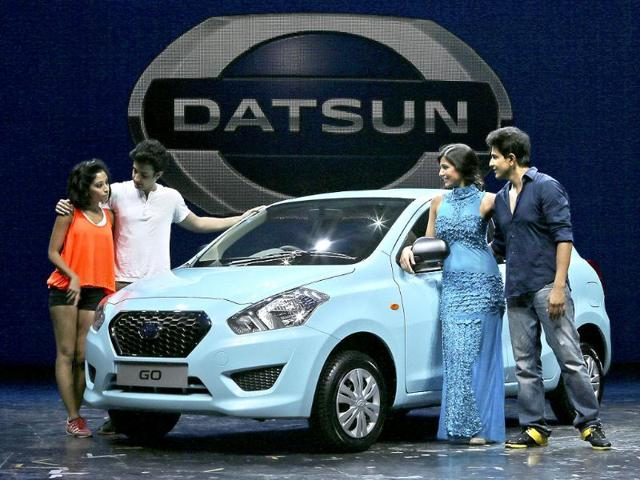 Artists pose with the newly launched Datsun Go car. The company hopes to fuel growth in emerging markets with a new generation of car buyers.(AP Photo)