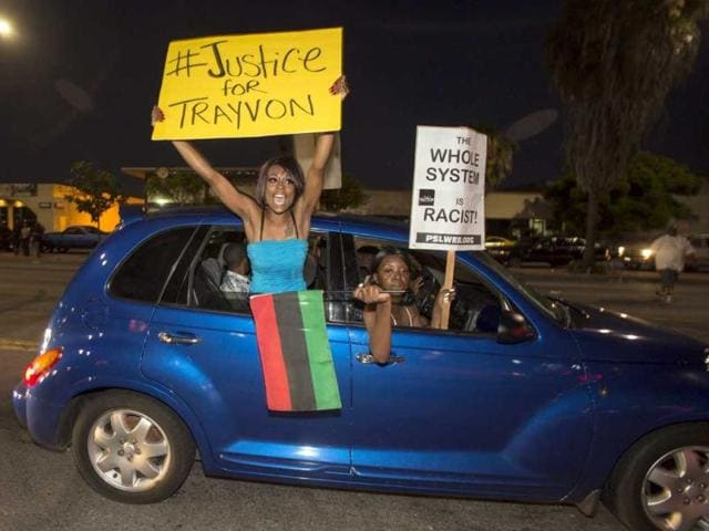 Demonstrators protest in a car on Crenshaw Boulevard during a protest in Los Angeles, the day after George Zimmerman was found not guilty in the shooting death of Trayvon Martin. (AP Photo)