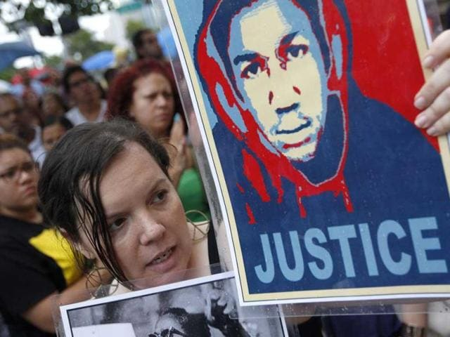 Annette Quintera from Miami holds an image of Trayvon Martin at a rally in Miami, Florida. (Reuters Photo)
