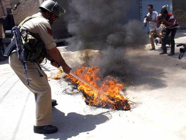 A policeman removing a burning tyre during a protest against the killing of locals by Border Security Force soldiers in Srinagar. (HT Photo/Waseem Andrabi)