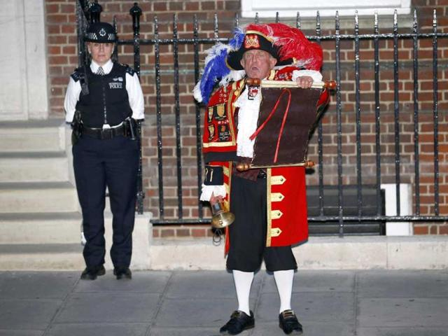 A town crier announces the royal birth outside the Lindo Wing of St Mary