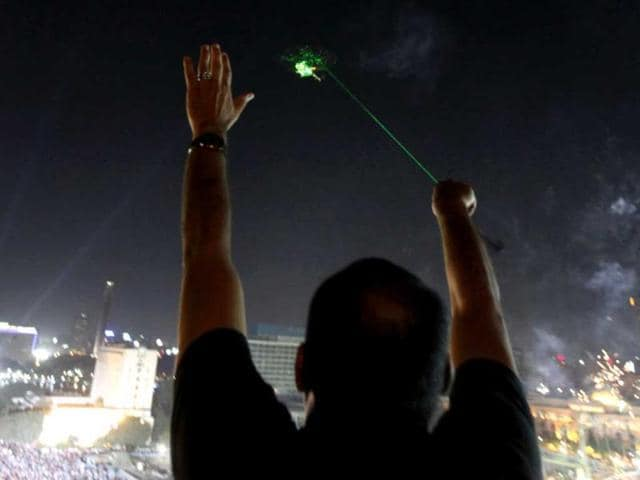 An anti-Mursi protester waves as a military helicopter passes over Tahrir square with lasers pointed at the helicopter during a mass protest to support the army in Tahrir square in Cairo, July 26, 2013. REUTERS
