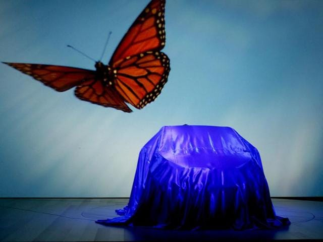Images are projected on to a screeen behind BMW's new i3 electric car just before it was unveiled in London. Reuters photo
