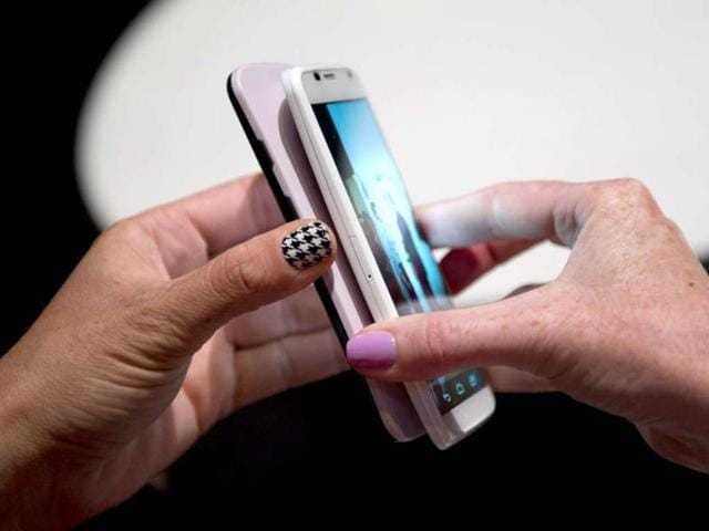 Two-Motorola-employees-tranfer-data-between-two-of-Motorola-s-Moto-X-as-the-American-manufactured-smartphone-is-unveiled-at-a-news-conference-in-New-York-Photo-AFP-Don-Emmert