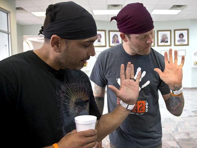 Pardeep-Kaleka-left-and-Arno-Michaelis-show-what-remains-of-tattoos-on-their-palms-at-the-gurdwara-of-Wisconsin-in-Oak-Creek-Wisconsin