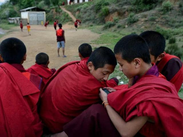 Buddhist-monks-look-at-a-smartphone-as-they-take-a-break-after-lunch-at-the-Dechen-Phodrang-Monastery-in-Thimphu-AFP-file-photo