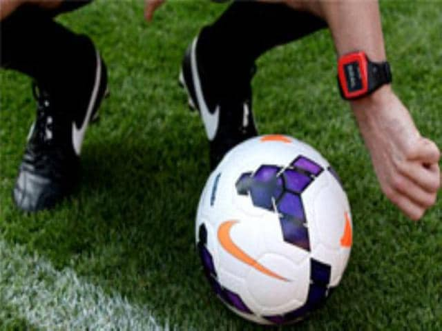 Referee-Anthony-Taylor-demonstrates-how-a-watch-notifies-referees-in-a-football-match-when-the-ball-crosses-the-goal-line-during-a-Goal-Line-Technology-presentation-at-the-Emirates-Stadium-London-AP-Photo