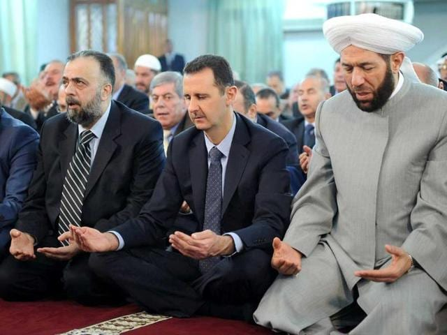 Syria-s-President-Bashar-al-Assad-2nd-R-attends-Eid-al-Fitr-prayers-at-Anas-bin-Malek-mosque-in-Damascus-in-this-handout-photograph-released-by-Syria-s-national-news-agency-SANA-Reuters