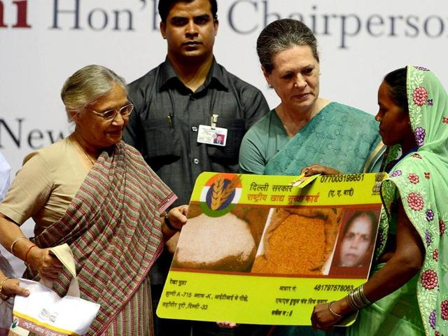 UPA-chief-Sonia-Gandhi-presents-a-recipient-with-an-ceremonial-oversized-food-card-as-Delhi-CM-Sheila-Dixit-looks-on-during-the-launch-of-the-food-security-programme-in-New-Delhi-AFP