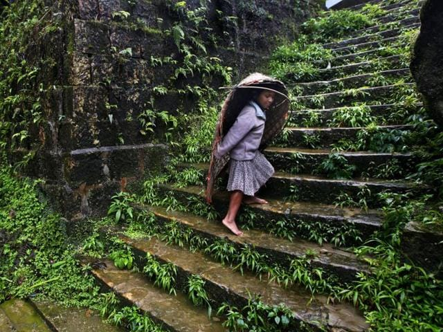 Aasheesh-Sharma-and-photographer-Raj-K-Raj-journeyed-to-Mawsynram-a-cluster-of-hamlets-in-Meghalaya-now-the-wettest-place-in-the-world-sorry-it-isn-t-Cherrapunji-They-got-drenched-but-returned-with-an-extraordinary-story-Home-and-dry-A-girl-in-Mawsynram-The-locals-don-t-bother-much-with-umbrellas-They-swear-by-the-knup-an-innovative-hands-free-rain-shield-that-lets-them-work-in-the-fields-dig-roads-and-carry-out-everyday-chores-without-having-to-grip-an-umbrella-pipe-The-rim-of-the-shield-looks-like-an-inverted-tear-drop-A-knup-extends-behind-the-head-and-also-keeps-the-rain-off-the-knees