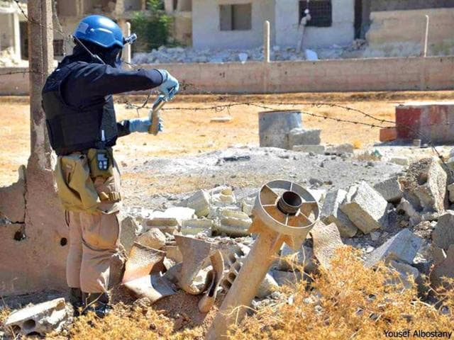 A-member-of-a-UN-investigation-team-takes-samples-of-sands-near-a-part-of-a-missile-is-likely-to-be-one-of-the-chemical-rockets-used-in-Syria-AP-Photo