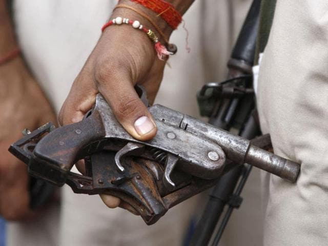 A policeman holds recovered arms during a door-to-door search operation in Muzaffarnagar, about 125 kilometers (78 miles) north of New Delhi, India. (AP Photo)