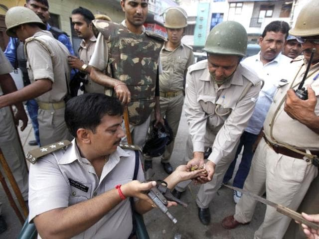 Policemen recover arms and ammunition during a door-to-door search operation in Muzaffarnagar, about 125 kilometers (78 miles) north of New Delhi. (AP Photo)