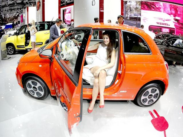 A hostess sits in a Fiat 500 during the first press day of the 65th Frankfurt Auto Show in Frankfurt, Germany. (AP Photo)